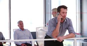 Hombre de negocios On Mobile Phone fuera de la sala de reunión almacen de metraje de vídeo