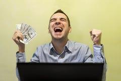Hombre de negocios moderno joven emocionado con su éxito mientras que trabaja imagen de archivo