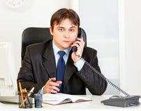 Hombre de negocios moderno pensativo que habla en el teléfono Imagenes de archivo