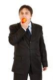 Hombre de negocios moderno que come la manzana grande Imágenes de archivo libres de regalías