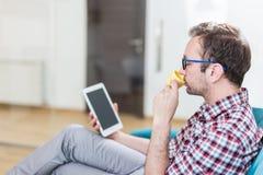 Hombre de negocios moderno que usa el dispositivo digital de la tableta mientras que se sienta en sofá y goza de su primera taza imagen de archivo