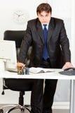 Hombre de negocios moderno terminante que se coloca en el escritorio de oficina Fotos de archivo