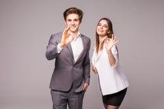 Hombre de negocios motivado y mujer que dan un gesto aceptable de la aprobación y del éxito como plantean de lado a lado el donan Fotografía de archivo