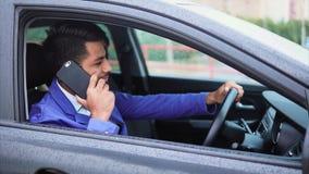 Hombre de negocios musulmán moderno joven que habla en smartphone en el coche metrajes