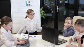 Hombre de negocios Near del niño un Flipchart que presenta un proyecto a los colegas almacen de video