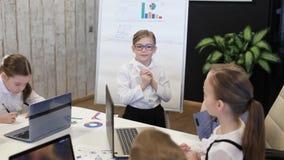Hombre de negocios Near del niño un Flipchart que presenta un proyecto a los colegas almacen de metraje de vídeo