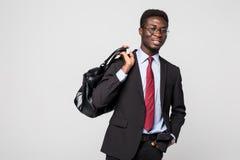 Hombre de negocios negro amistoso que camina con su bolso que sonríe y feliz en fondo gris Foto de archivo libre de regalías