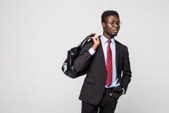 Hombre de negocios negro amistoso que camina con su bolso que sonríe y feliz en fondo gris Imagen de archivo libre de regalías