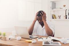 Hombre de negocios negro cansado en la oficina, trabajo con el ordenador portátil Foto de archivo
