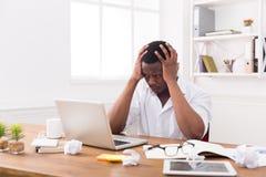 Hombre de negocios negro cansado en la oficina, trabajo con el ordenador portátil Fotos de archivo libres de regalías