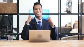 Hombre de negocios negro Celebrating Success, trabajando en el ordenador portátil Imagen de archivo libre de regalías