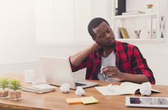 Hombre de negocios negro con exceso de trabajo en la oficina casual, trabajo con el ordenador portátil Foto de archivo libre de regalías