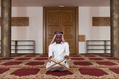 Hombre de negocios negro In Dishdasha Is que lee el Quran Fotos de archivo libres de regalías