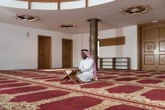 Hombre de negocios negro In Dishdasha Is que lee el Quran Fotografía de archivo libre de regalías