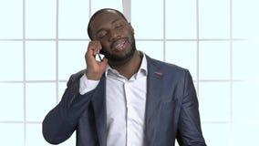Hombre de negocios negro en el traje que tiene conversación telefónica almacen de video