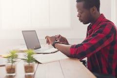 Hombre de negocios negro en la oficina casual, trabajo con el ordenador portátil Fotografía de archivo libre de regalías