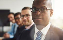 Hombre de negocios negro hermoso con tres empleados Fotos de archivo