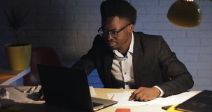 Hombre de negocios negro joven cansado y subrayado que trabaja con el ordenador port?til en la oficina de la noche Freelancer que metrajes