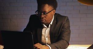 Hombre de negocios negro joven con el ordenador port?til y los papeles que trabajan en la oficina de la noche ?l firma los docume metrajes