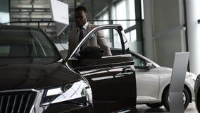 Hombre de negocios negro joven en fondo auto del salón Venta del coche y concepto del alquiler Hombre afroamericano rico almacen de video