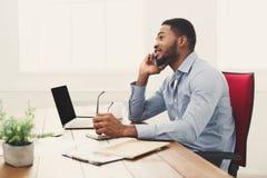 Hombre de negocios negro joven que habla en el teléfono móvil foto de archivo