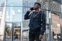 Hombre de negocios negro joven que habla en el teléfono móvil y el trabajo Hombre de negocios africano barbudo feliz que usa el t imágenes de archivo libres de regalías