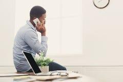 Hombre de negocios negro joven que tiene charla del teléfono imagen de archivo
