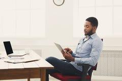 Hombre de negocios negro joven que trabaja con la tableta fotografía de archivo libre de regalías
