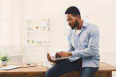 Hombre de negocios negro joven que trabaja en el ordenador portátil en la oficina foto de archivo