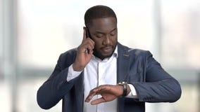 Hombre de negocios negro ocupado que designa una reunión por el teléfono almacen de video