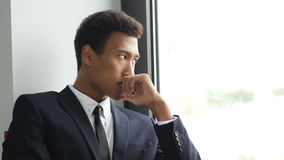 Hombre de negocios negro pensativo de pensamiento en el traje, mirando a través de ventana