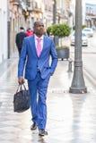 Hombre de negocios negro que camina en la calle con una cartera moderna Foto de archivo libre de regalías