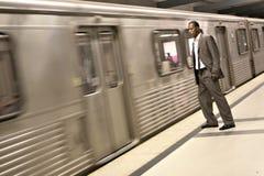 Hombre de negocios negro que mira el metro entrenar al paso Imagen de archivo libre de regalías