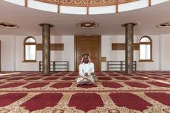Hombre de negocios negro Reading The Koran Imagenes de archivo