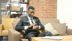 Hombre de negocios negro Using Smartwatch, interior almacen de metraje de vídeo