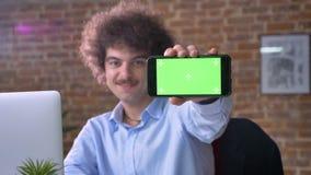 Hombre de negocios nerdy divertido con el pelo rizado del volumen que señala el teléfono con llave de la croma en cámara, sentánd almacen de video