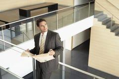 Hombre de negocios With Newspaper Leaning en la verja de cristal imagen de archivo