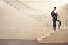 Hombre de negocios With Newspaper Standing en pasos fotos de archivo