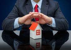 Hombre de negocios o agente de la propiedad inmobiliaria y sostener una casa modelo imagenes de archivo