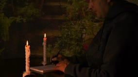 Hombre de negocios o estudiante caucásico del hombre que se sienta en la tabla en la noche La luz de una vela ilumina el cuaderno