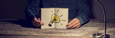 Hombre de negocios o estudiante que muestra su cuaderno de trabajo con un handd Foto de archivo libre de regalías