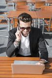 Hombre de negocios o trabajador en traje negro en la tabla y el hablar masculinos en el teléfono Imagenes de archivo