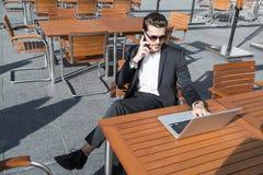 Hombre de negocios o trabajador en traje negro en la tabla y el hablar masculinos en el teléfono Fotografía de archivo