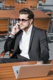 Hombre de negocios o trabajador en traje negro en la tabla y el hablar masculinos en el teléfono Foto de archivo libre de regalías