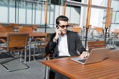 Hombre de negocios o trabajador en traje negro en la tabla y el hablar masculinos en el teléfono Fotos de archivo libres de regalías
