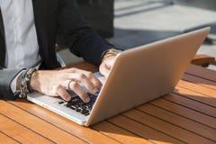 Hombre de negocios o trabajador en traje negro en la tabla y el mecanografiar masculinos en el ordenador Imagenes de archivo