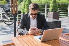 Hombre de negocios o trabajador en traje negro en la tabla y mirada masculinos en el teléfono Imagen de archivo