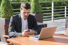 Hombre de negocios o trabajador en traje negro en la tabla y mirada masculinos en el teléfono Fotos de archivo