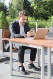 Hombre de negocios o trabajador en traje negro en la tabla y mirada masculinos en el teléfono Fotografía de archivo