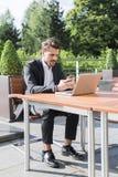 Hombre de negocios o trabajador en traje negro en la tabla y mirada masculinos en el teléfono Foto de archivo libre de regalías